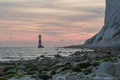 19/09/2018 Eastbourne, het Verenigd Koninkrijk Kiezelachtige Hoofdvuurtoren in het overzees en de zonsondergang op de achtergrond royalty-vrije stock afbeelding