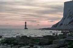19/09/2018 Eastbourne, het Verenigd Koninkrijk Kiezelachtige Hoofdvuurtoren in het overzees en de zonsondergang op de achtergrond stock afbeeldingen
