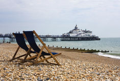 Eastbourne Pier. Eastbourne beach Looking at the Pier and two deck chairs Royalty Free Stock Images