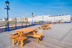 Eastbourne Pier. Benches, for pic-nic lamps and Eastbourne in the background on Pier with nobody during a sunny day - UK Sussex 05/2016 Stock Photos