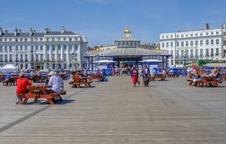 Eastbourne Pier, people strolling and sitting on picnic benches on a blue sky summer`s afternoon. Eastbourne, Sussex, England, UK - August 1, 2018: People royalty free stock photo