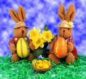 Easter. Two hares with easter eggs, daffodils and chicken in nest Stock Photo