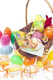 Easter. Setup with small basket full of eggs, bunny and eggs candle Royalty Free Stock Photo