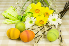 Easter. Green easter eggs with a bunch of spring flowers Stock Photos