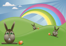 Easter. Brown bunnies and Easter eggs in the spring landscape with rainbow Stock Image