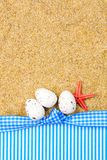 Easter abstract gift card on sand textured background with easter eggs laying in row and red starfish as spring vacation theme royalty free stock photos