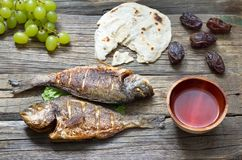 Easter ancient food with fish passover bread and goblet of wine last supper concept. On planks Stock Images