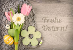 Easter arragement and caption. Easter arragement with flowers and eggs on wood with caption Frohe Ostern! (Happy Easter in German stock image