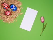 Easter arrangement with Easter basket, wood, eggs, white paper, flower royalty free stock images