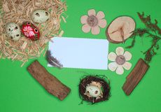 Easter arrangement with Easter basket, wood, eggs, white paper, wooden flowers. Grass Royalty Free Stock Images