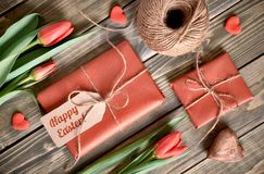 Easter arrangement: red tulips, wrapped gifts, cord and decorati Royalty Free Stock Photo
