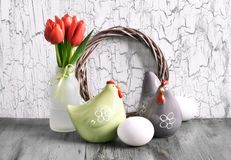 Easter arrangement with wooden wreath, red tulips, ceramic hens. Easter decorations on gray rustic background. Arrangement with wooden wreath, red tulips Stock Images