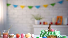 Easter art school, dyed eggs in basket, chocolate bunny and paints on table. Stock photo royalty free stock photo