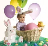 Easter baby. A baby dressed in bunny ears sits in a basket surrounded by Easter eggs and balloons royalty free stock photography