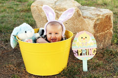 Easter baby with bunny ears. Four-month-old Easter bunny and adorable baby with bunny ears. Baby is smiling and sitting inside a bright yellow bucket with a stock image