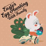 Easter baby bunny in overalls holding big decorated egg, isolated whire rabbit with ears hunting eggs sitting under a Stock Photography