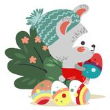 Easter baby bunny in overalls holding big decorated egg, isolated whire rabbit with ears hunting eggs sitting under a Royalty Free Stock Photo