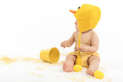 Easter Baby in Duck Costume. Baby girl wearing duck or chicken hat and diaper cover looking aside, studio isolated royalty free stock image