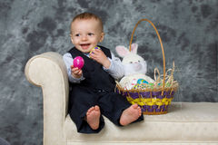 Easter baby. Happy Easter basket baby playing with eggs in studio Stock Image
