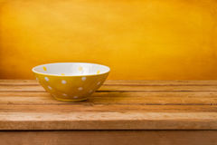Easter background. Empty yellow bowl with dots on wooden table. Easter background royalty free stock image