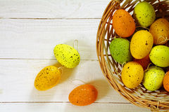 Easter background, basket with eggs in green, orange and yellow Royalty Free Stock Photography