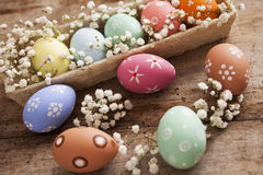 Easter background. Beautiful colorful eggs with spring flowers Stock Photos