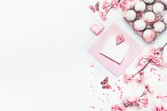 Easter background with blank greeting card mock up , pastel pink spring blossom flowers, eggs and hearts on white, top view. Copy royalty free stock photos