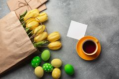 Easter background with blue, green eggs and a cup of tea in nest and yellow tulips. Top view with copy space royalty free stock photo