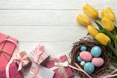 Easter background with blue and pink eggs in nest, gifts and yellow tulips stock images