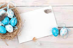 Easter background with blue and white eggs in nest and greeting royalty free stock photography