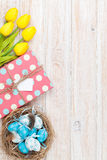 Easter background with blue and white eggs in nest, yellow tulip royalty free stock images