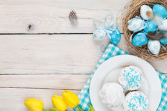 Easter background with blue and white eggs in nest, yellow tulip stock image