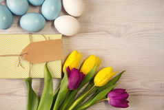 Easter background with blue and white eggs and purple and yellow tulips Stock Photo