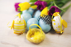 Easter background with blue and white eggs and purple and yellow tulips Royalty Free Stock Photos