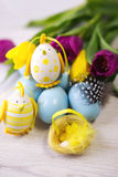Easter background with blue and white eggs and purple and yellow tulips Stock Image