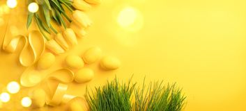 Easter background. Bright yellow eggs and bunch of spring blooming tulip flowers over yellow background royalty free stock image