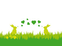 Easter background with bunnies blowing valentines. Easter vector illustration with silhouettes of two bunnies blowing valentines at each other, eggs and grass Royalty Free Stock Photo