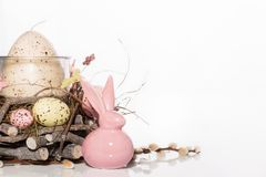 Easter background-Easter Bunny and decorated candlestick in the shape of a nest with quail eggs stock photos
