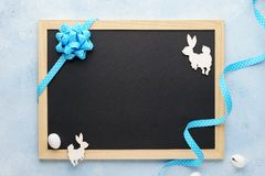 Easter background with chalkboard, blue ribbon and cute bunny stock photos