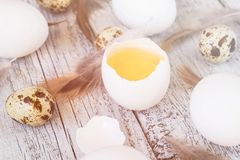 Easter background with chicken quail one broken eggs and feathers on white wooden table, food top view. Toned Stock Photos