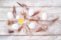 Easter background with chicken quail one broken eggs and feathers on white wooden table, food top view. Toned Stock Photography