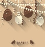 Easter background with chocolate eggs, serpentine and bunting fl Stock Photos