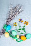 Easter background with clolrful eggs, pussy-willow and paper flo. Pussy willow with lovely polka dot ribbon, painted eggs and hand made paper flowers on blue Royalty Free Stock Photography