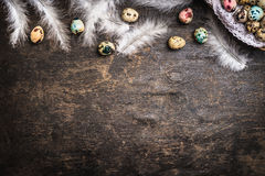 Easter background with colored eggs, feathers and basket, top view royalty free stock images