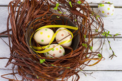 Easter background with colored eggs in the nest and white boards Stock Photo