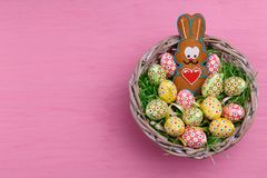 Top view of Easter eggs and a gingerbread in the shape of a rabbit in a wicker basket on a bright pink background. Stock Image