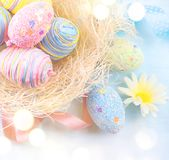 Easter background. Colorful eggs with decorations over blue wooden background Stock Photos