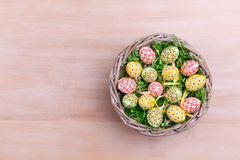 Top view of Easter eggs and feathers in a wicker basket on a wooden background. Easter greetings card. Royalty Free Stock Photos