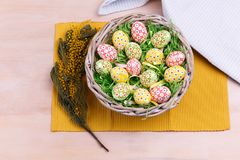 Top view of Easter colorful eggs in a wicker basket on a wooden background. Easter greeting card. Royalty Free Stock Images
