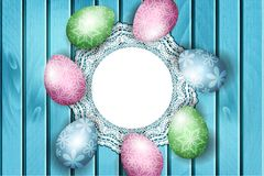 Easter background, colorful painted eggs laying on blue wooden board Stock Photos